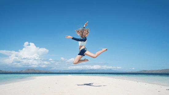 Milujeme Kameny - radost - dívka ve výskoku na pláži
